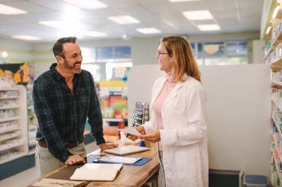 male customer and female pharmacist smiling